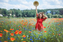 Lovely Young Romantic Woman In Straw Hat On Poppy Flower Field Posing On Background Summer. Wearing Straw Hat. Soft Colors
