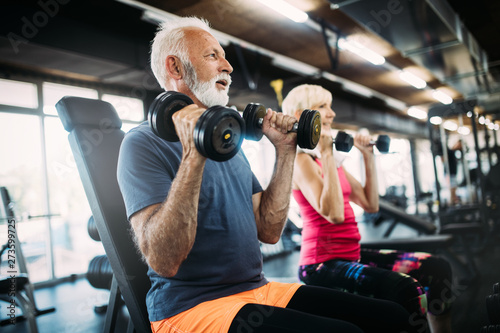 Poster Fitness Happy senior people doing exercises in gym to stay fit