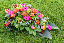 Colorful Flower Arrangement On Green Grass Field. All Saints Flower Arrangements, Flowers For Graveyard And Funeral.