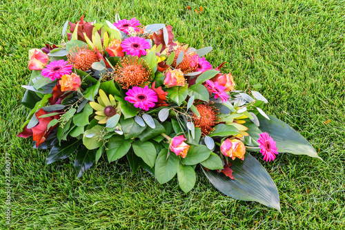 Fotomural Colorful flower arrangement on green grass field