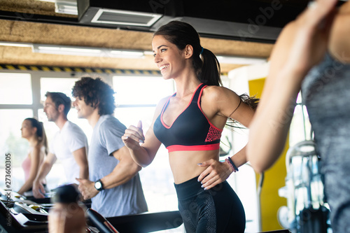fototapeta na drzwi i meble Happy fit people running on treadmill at fitness gym club