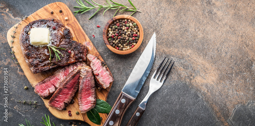 Medium rare Ribeye steak with herbs and a piece of butter on the wooden tray Canvas-taulu