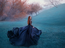 Charming Lady With Red Hair On Green Hill, Scraping Widow In Long Black Flying Dress And Lace Blouse Turns Into Flower, Young Sorceress Looking For Herbs In Autumn Cold Forest, Creative Colors