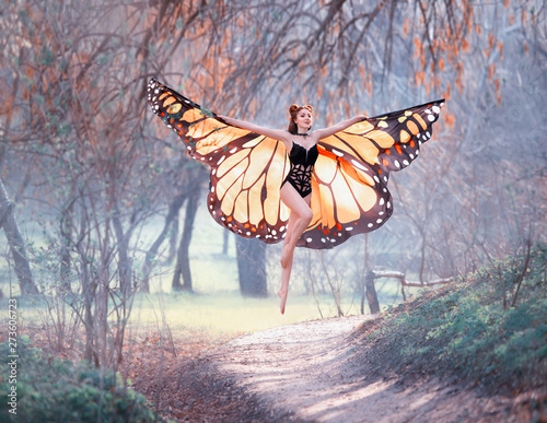 Fototapeta  a joyful girl with big bright orange wings walks in the early trenched spring fo