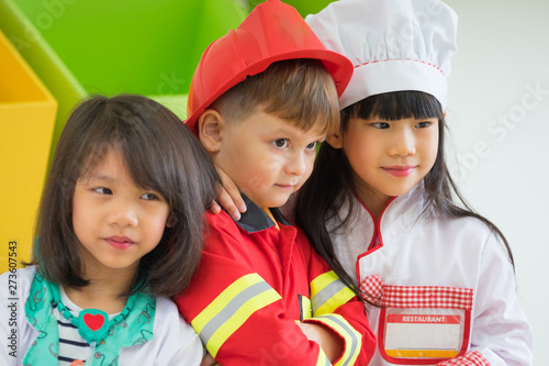Three kid dress up to fireman and doctor and chef at roll play classroom,Kinderg Fototapeta
