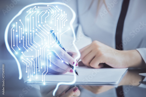 Multi exposure of woman's writing hand on background with brain hud. Concept of learning.