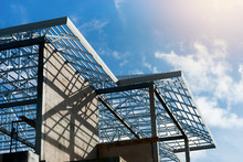 Roof Frame Of Under Construction House..Metal Roof Frame Structure Of A Two Story House Without  Roof Tiles Under Sunny Cloud Blue Sky,low Angle View.
