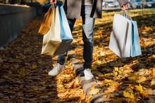 Autumn Fun. Cropped Shot Of Man Walking With Shopping Bags, Enjoying Fall Season With Yellow Leaves Covering Sidewalk.