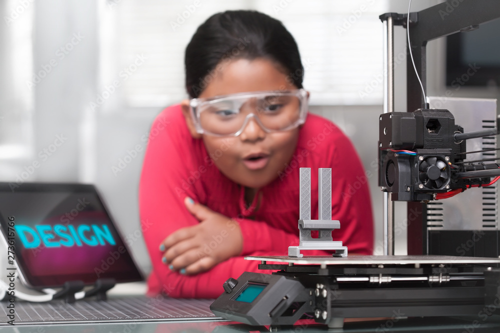 Fototapety, obrazy: An young hispanic girl is amazed as she looks at her 3d printed project in a STEM summer class.