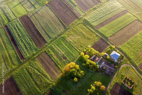 Foto auf AluDibond Pistazie Top view of rural landscape on sunny spring day. Farm cottage, house and barn on green and black field copy space background. Drone photography.
