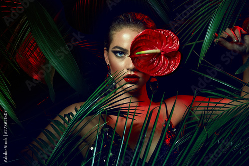 A beautiful tanned girl with natural make-up and wet hair stands in the jungle among exotic plants Fototapet