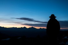 Silhouette Of Man In Hat Looking Mountains At Dawn, Aosta Valley, Italy, Europe