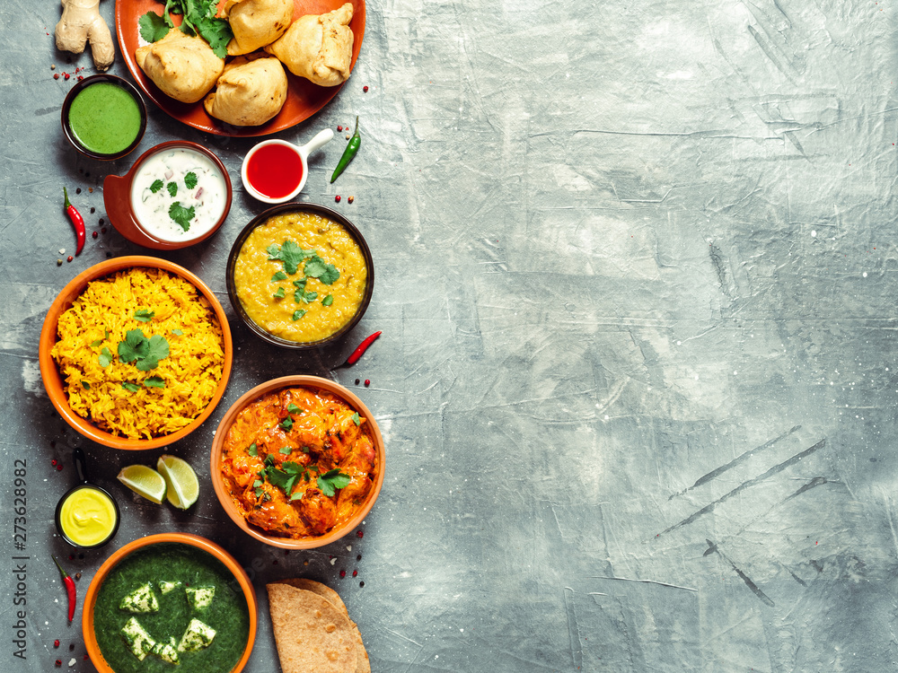 Fototapeta Indian cuisine dishes: tikka masala, dal, paneer, samosa, chapati, chutney, spices. Indian food on gray background. Assortment indian meal with copy space for text. Top view or flat lay.
