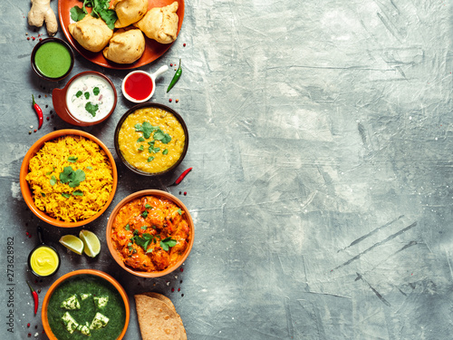 Fototapeta Indian cuisine dishes: tikka masala, dal, paneer, samosa, chapati, chutney, spices. Indian food on gray background. Assortment indian meal with copy space for text. Top view or flat lay. obraz