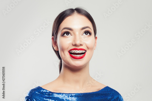 Stampa su Tela  Portrait of happy beautiful woman in braces on white background