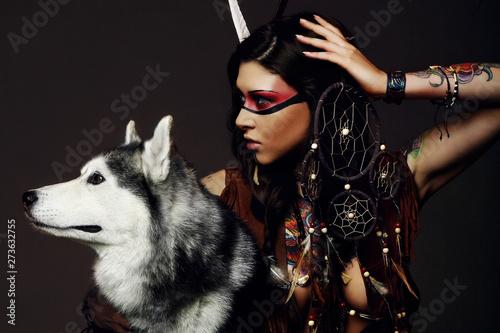 Beautiful woman in native american costume posing in a studio with husky dog Fototapeta