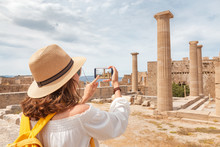 Tourist Girl Taking Photos And Selfie Of Tourist Landmark Of Ancient Acropolis Town. Travel Destinations And Sightseeing Tours