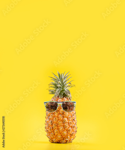 Creative pineapple looking up with sunglasses and shell isolated on yellow background, summer vacation beach idea design pattern, copy space close up Wall mural