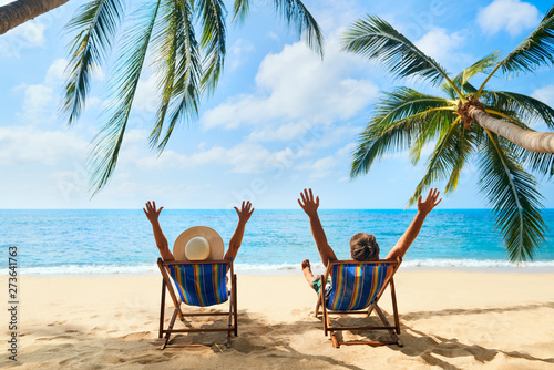 Poster de jardin Detente Happy couple with arms up relax on the beach enjoy beautiful sea on the tropical island