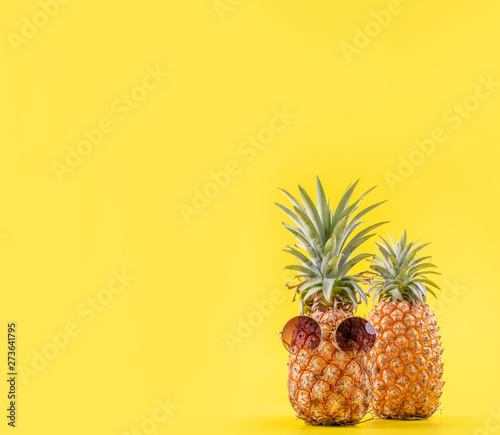 Creative pineapple looking up with sunglasses and shell isolated on yellow background, summer vacation beach idea design pattern, copy space close up - 273641795