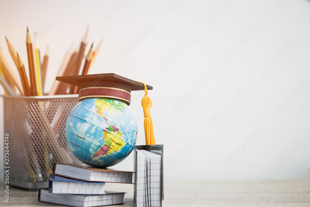 Fototapeta Concept of global business study abroad education. Graduation hat on models globe, books with pencils on wood white background. Congratulations to graduated, Studies lead to success. Back to School