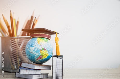 Obraz Concept of global business study abroad education. Graduation hat on models globe, books with pencils on wood white background. Congratulations to graduated, Studies lead to success. Back to School - fototapety do salonu