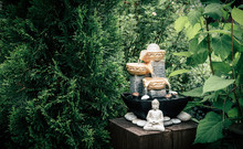 Small Home Garden Private Fountain With Meditating Buddha Statue Between Trees And Bushes. Private Zen Garden Concept.
