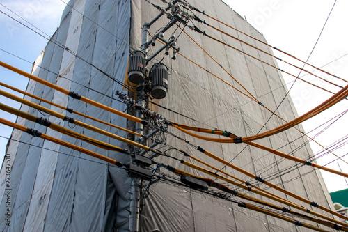 工事中のビルと絶縁カバーをした電線 © decoplus
