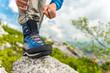 Leinwandbild Motiv Male Hiker Tying Boot Laces