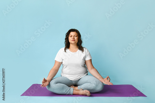 Photo Beautiful plus size woman meditating on color background