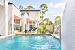 Luxury pool side near modern home entrance.