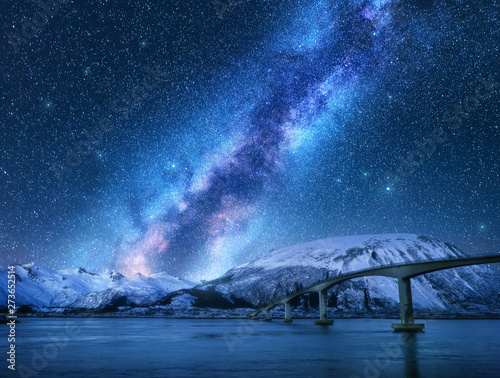 Photo Bridge and starry sky with Milky Way over snow covered mountains reflected in water