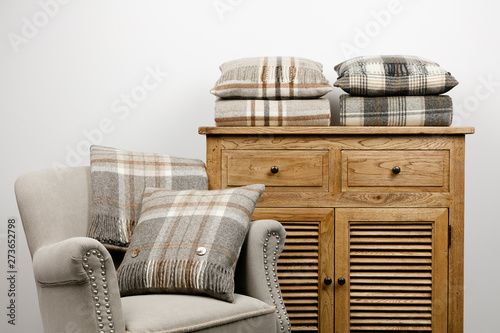 Fotografie, Obraz  Chair and side cabinet with natural coloured checked cushions and throws