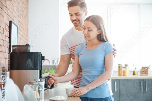 Fotografia  Young couple using coffee machine in kitchen