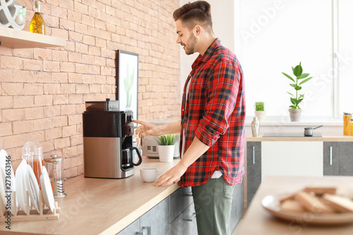 Montage in der Fensternische Kaffee Handsome man using coffee machine in kitchen