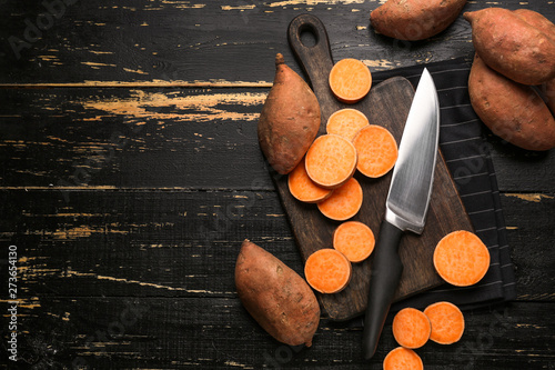Foto Cutting board and knife with raw sweet potato on wooden background