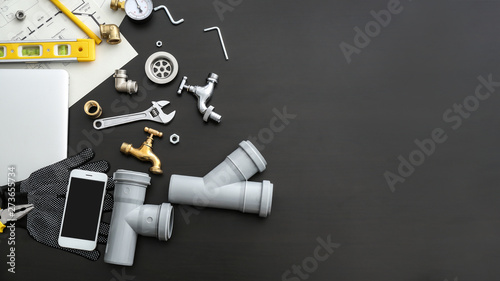 Fotomural Mobile phone with plumbing items on dark background
