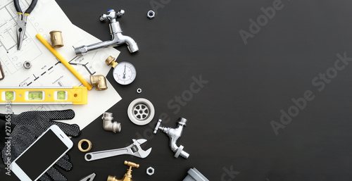 Cuadros en Lienzo Mobile phone with plumbing items on dark background