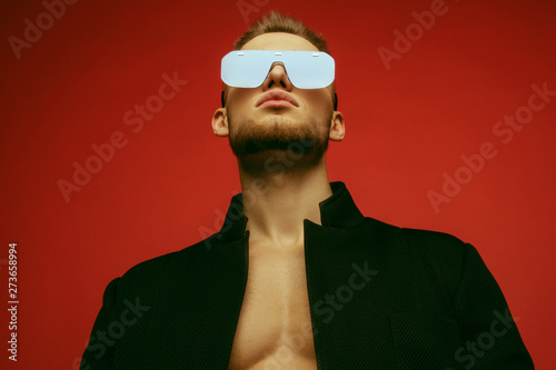 Fototapeta Muscle strong face beautiful stripped male model in casual look with denim and suit wearing glasses on bordo red isolated font background obraz na płótnie