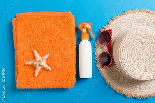 Summer beach flat lay accessories. Sunscreen bottle cream, towel and seashells on colored Background. Travel holiday concept with copy space