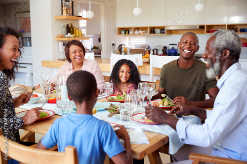 Fotomural  Multi-Generation Family Sitting Around Table At Home Enjoying Meal Together
