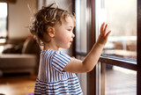 A toddler girl standing by window indoors at home, looking out.