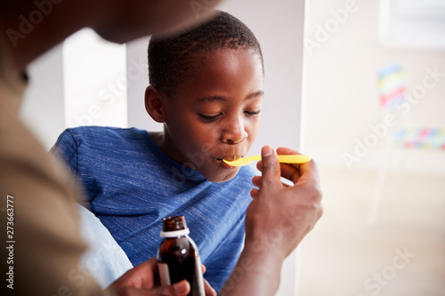 Fotografia  Father Giving Sick Son Ill In Bed Medicine From Bottle