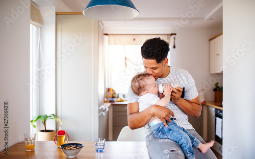A father bottle feeding a small toddler son indoors at home. Wallpaper Mural