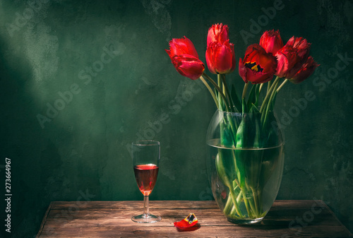 Fototapeta Classic still life with beautiful red tulip flowers bouquet in transparent glass vase and a glass of red wine. Art photography. obraz