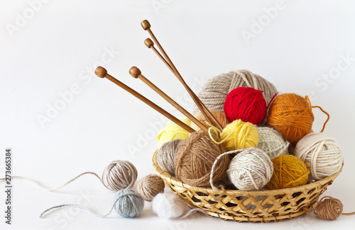 Fotografia, Obraz Сolorful balls of wool yarn and knitting wooden needles in a wicker basket on a white background