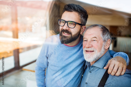 Adult son and senior father indoors at home, looking out Poster Mural XXL