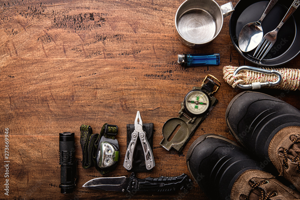 Fototapety, obrazy: Outdoor travel equipment planning for a mountain trekking camping trip on wooden background. Top view - vintage film grain filter effect styles