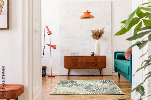Obraz Stylish compositon of retro home interior with vintage cupboard, velvet sofa, flowers in vase, design orange lamps , elegant accessories and abstract paintings. Minimalistic concept. Nice home decor.  - fototapety do salonu
