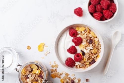 Fotografia Greek yogurt in bowl with raspberries and muesli on white table top view